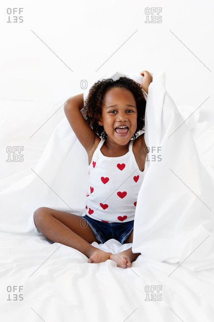 Girl playing in white sheets on bed