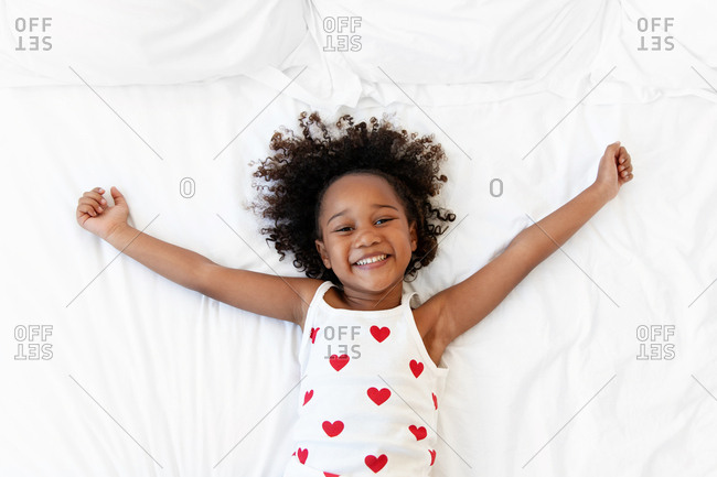 Portrait of a smiling girl with frizzy hair and outstretched arms