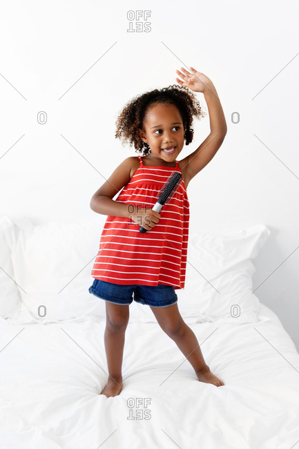 Girl standing on bed with arm raised singing into hairbrush and pretending it is a microphone