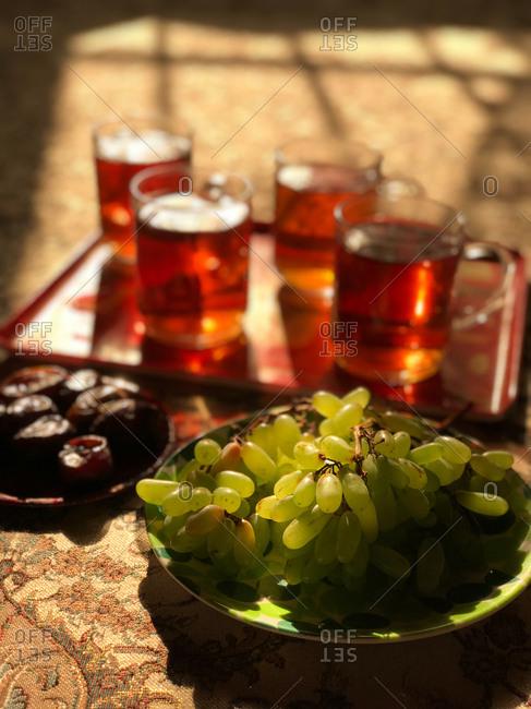 Servings of fruit and tea in golden sunlight