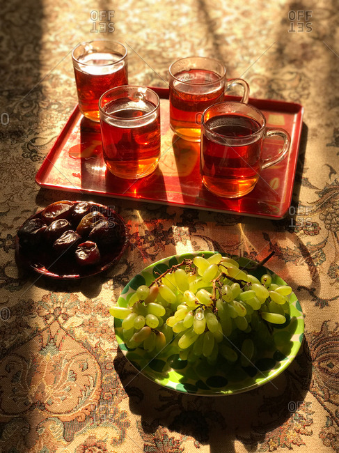 Servings of fruit and tea in golden sunlight