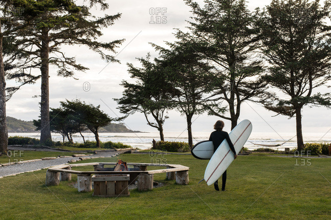 Surfer at park carrying two surfboards toward the beach
