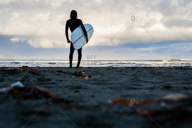 Silhouette of surfer standing on beach and holding surfboard