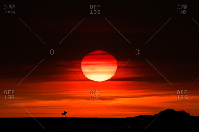 Silhouette of distant surfer carrying surfboard at sunset on the coast