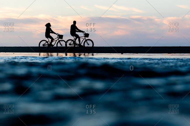 Silhouette of couple riding bicycles together along the coast