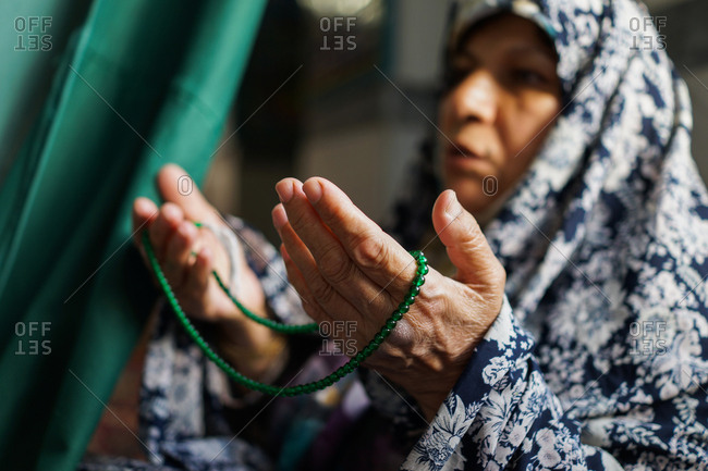 Muslim woman praying with prayer beads