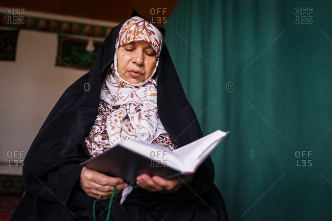 Muslim woman reading the quran in a mosque