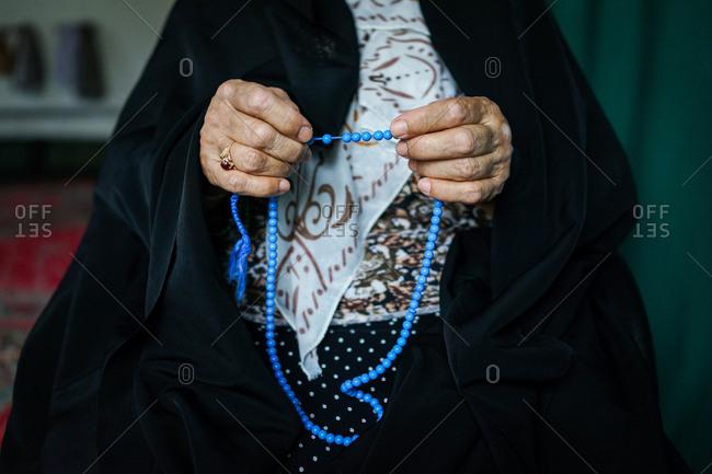 Close-up of a woman's hands holding blue muslim prayer beads