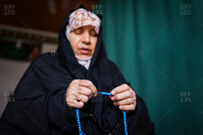 Muslim woman praying with blue prayer beads