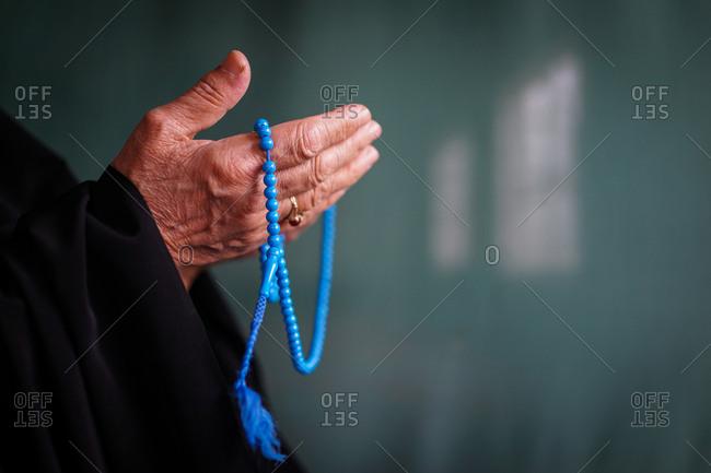 Close-up of a woman's hands holding muslim prayer beads