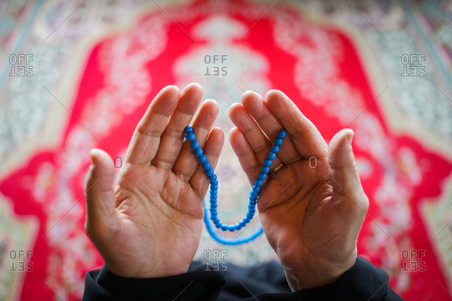 Overhead view of hands holding prayer beads in a mosque