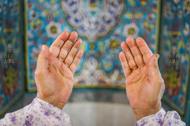 Outstretched hands of Muslim woman praying in a beautiful mosque