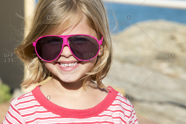 Portrait of a pretty little smiling blond girl with glasses of pink adult.