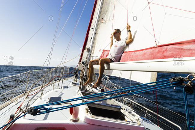 August 25, 2017: A man sitting on the boom of a sailing boat on the sea, Trinidad and Tobago, Antilles, West Indies, South America
