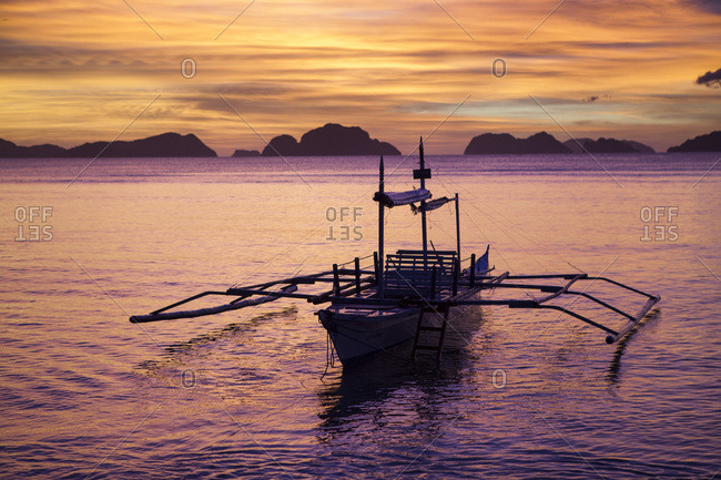 Sunset and trimaran in Bacuit Bay, Palawan Island, Philippines