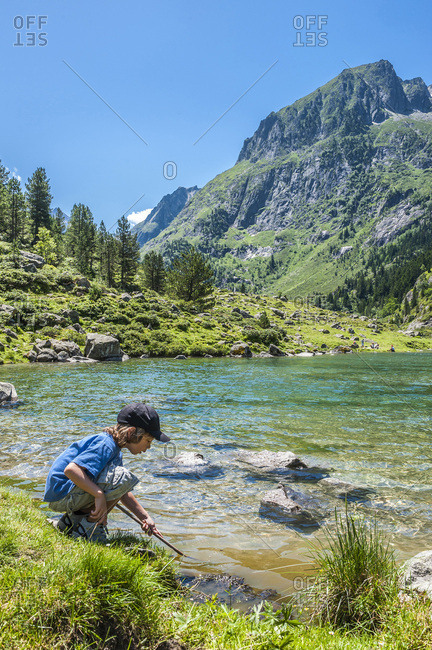 France, Pyrenees National Park, Occitanie region, Val d'Azun, 6-year-old boy by the Suyen lake on the gave d'Arrens (name referring to torrential rivers, in the west side of the Pyrenees)