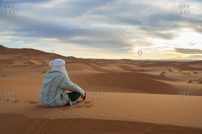 Berber man sitting in the dunes of Merzouga watching the sunset, Morocco