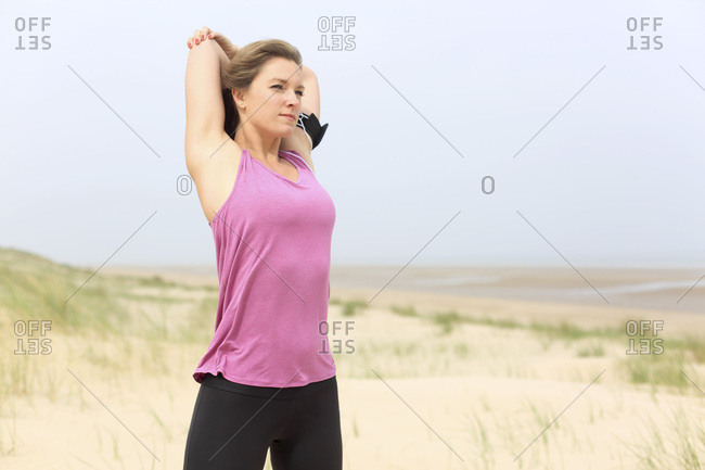 Young woman on the beach. Stretching