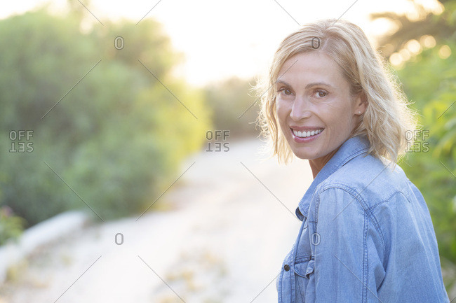 Portrait of a smiling blonde woman in a path.