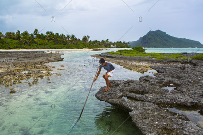 February 10, 2018: Terevau, 11, fishing with a harpoon in front of his home, Motu Tiapaa, Maupiti Island, Leeward Islands, French Polynesia