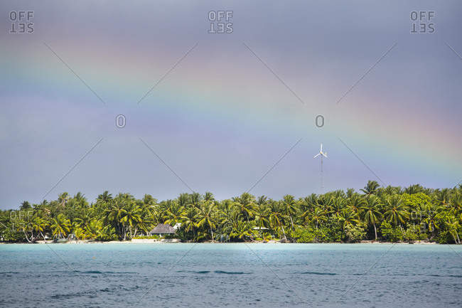 Rainbow above the Motu (islet) where the Maupiti airport and coconut grove are located seen from the lagoon, Leeward Islands, French Polynesia