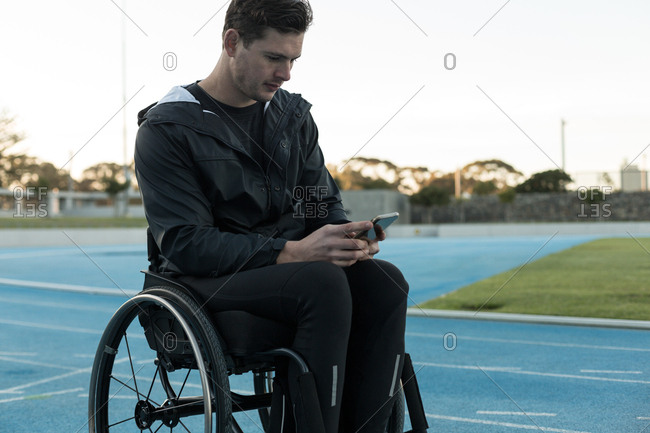 Young disabled athletic using mobile phone at sports venue