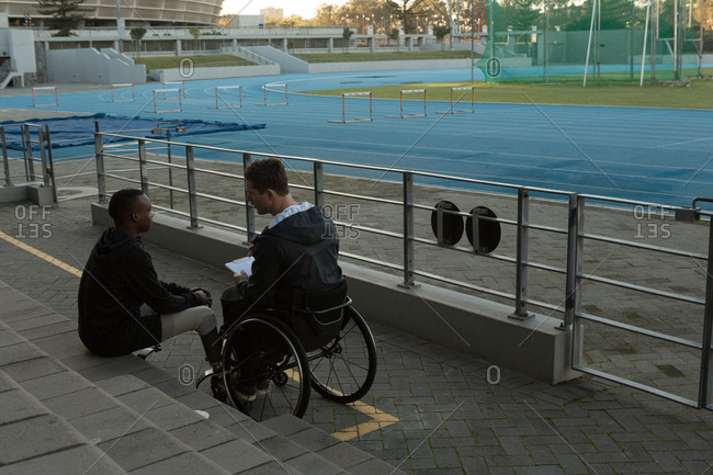 Two disabled athletics discussing over clipboard at sports venue