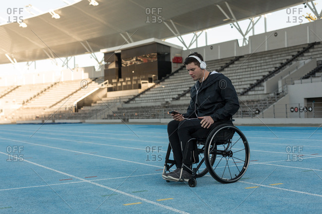 Disabled athletic listening music on headphones at sports venue