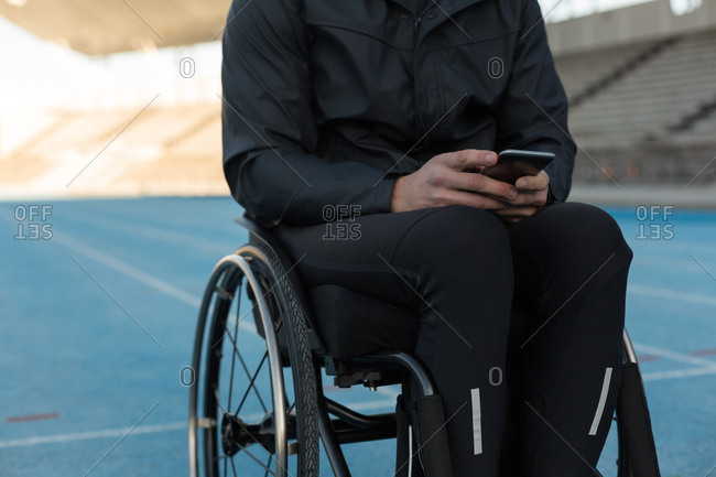 Mid section of disabled athletic using mobile phone at sports venue