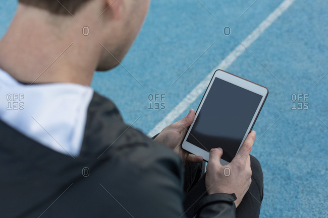 Close-up of disabled athletic using digital tablet at sports venue