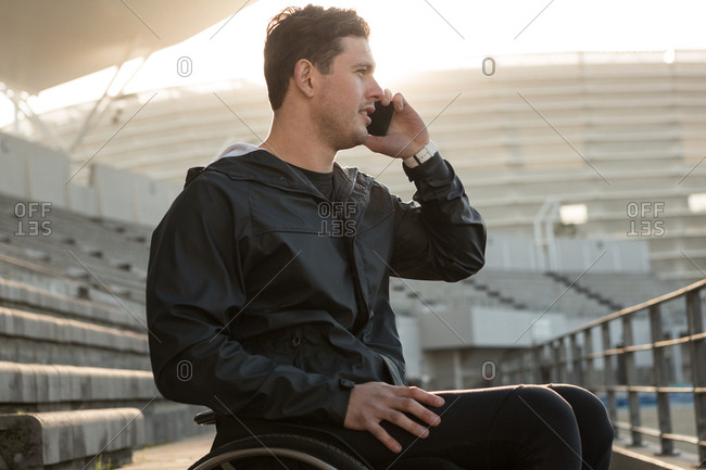 Disabled athletic talking on mobile phone at sports venue