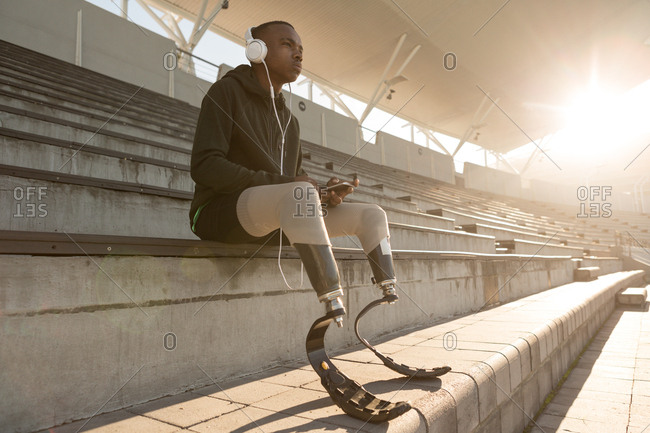 Disabled athletic listening music on mobile phone at sports venue