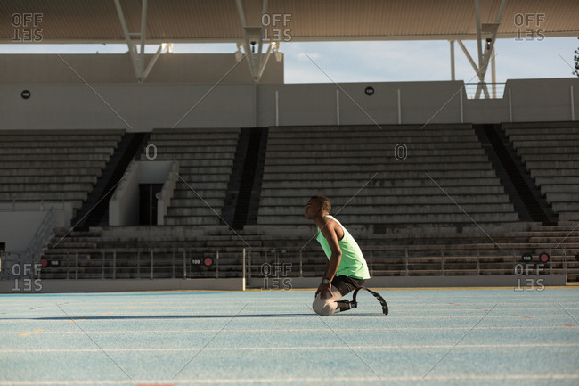 Side view of disabled athletic relaxing on a running track