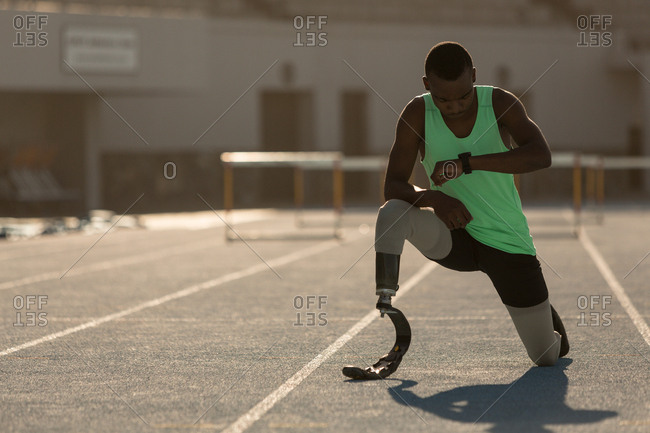 Male disabled athletic checking time on a running track
