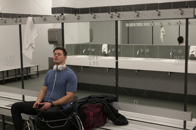 Disabled man listening music on headphones inc hanging room