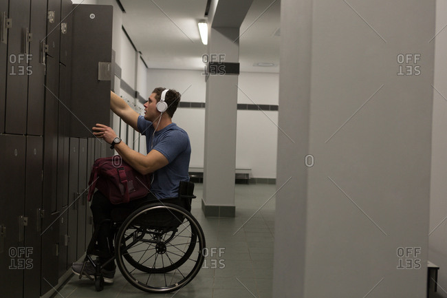 Disabled man listening music on headphones in changing room