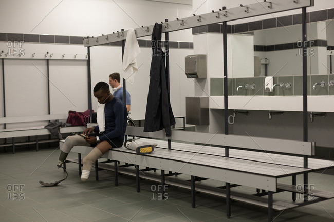 Two disabled athletics relaxing together in changing room