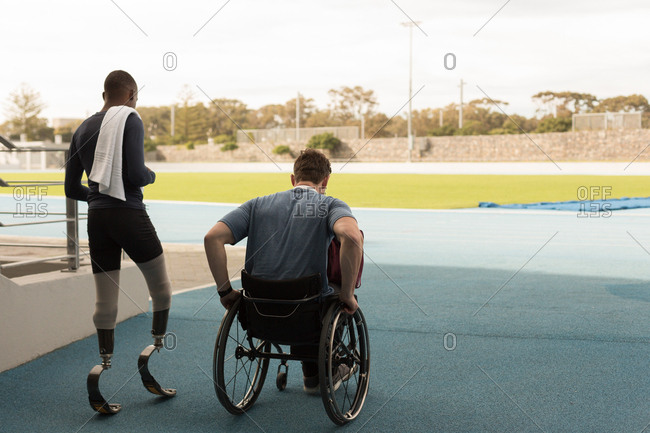 Rear view of two disabled athletics walking together on sports venue