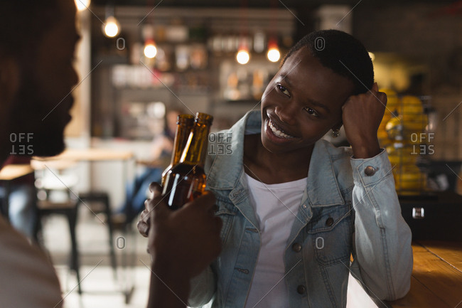Happy couple toasting beer bottle in cafe