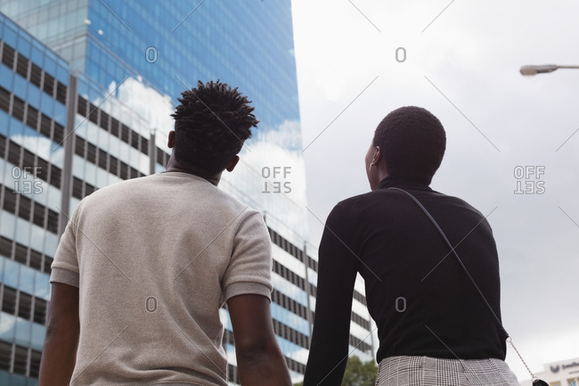 Rear view of couple standing in city street