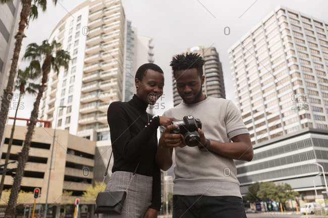 Man reviewing photos on digital camera in city street