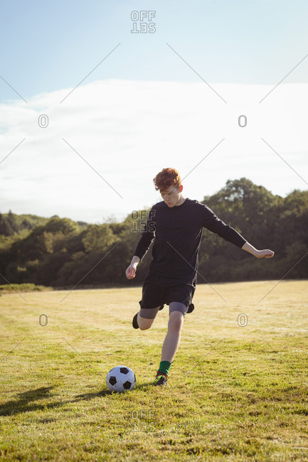 Football player kicking football in the field on a sunny day