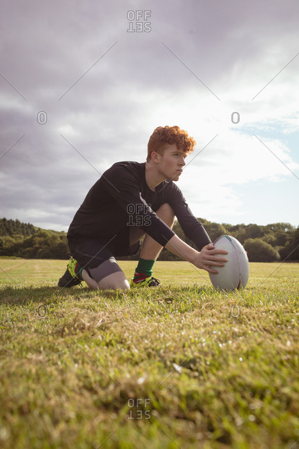 Rugby player placing rugby ball in the field on a sunny day