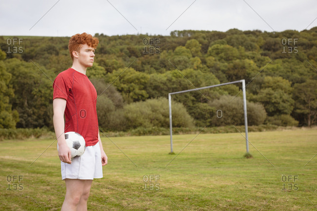 Young football player standing with soccer ball in the field