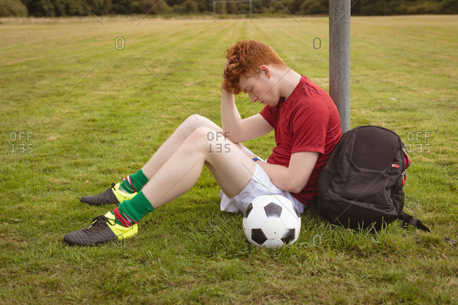 Young football player relaxing in the field