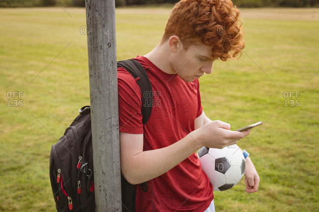 Young football player using mobile phone in the field