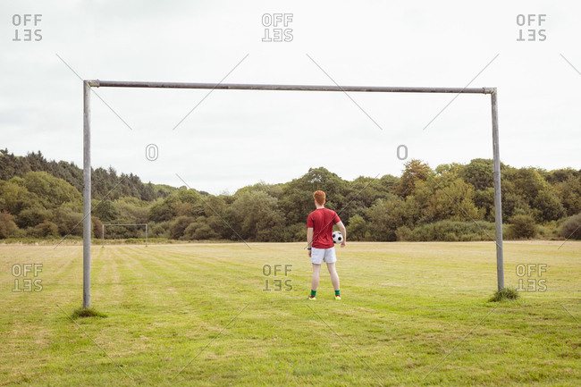 Rear view of football player standing with soccer ball in the field