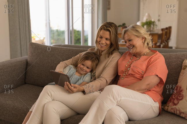 Multi-generation family using digital tablet in living room at home