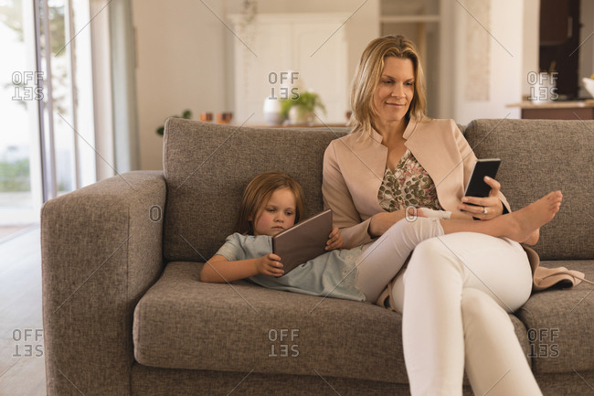 Mother and daughter using digital tablet and mobile phone in living room at home
