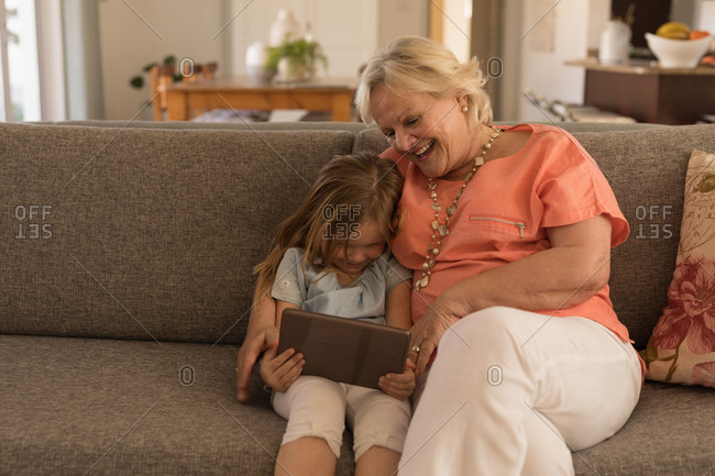 Grandmother and granddaughter using digital tablet in living room at home